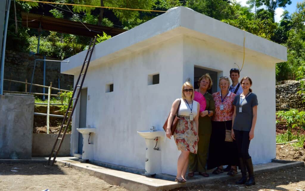 Anita Hummel with team of Project Sprouts outside a toilet they raised funds for an impoverished Elementary School in Lao Cao Vietnam.
